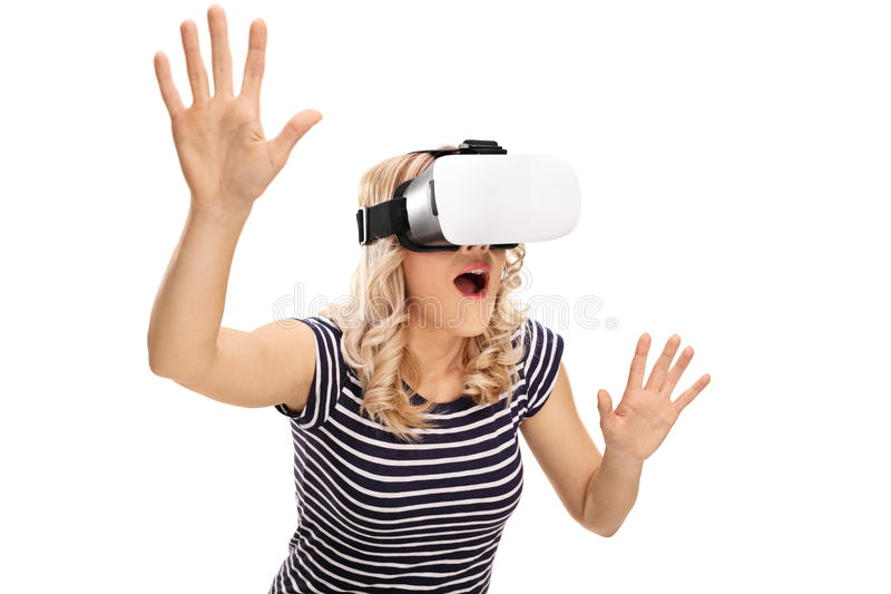 Amazed woman experiencing virtual reality. Young amazed woman experiencing virtual reality isolated on white background royalty free stock images