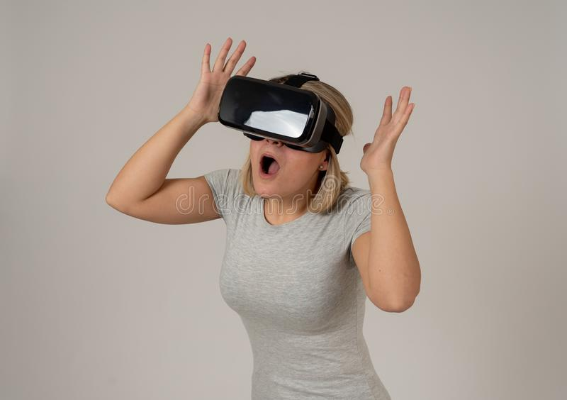 Portrait of cheerful and shocked young woman wearing Virtual Reality headset exploring 3D world. Amazed woman getting experience using VR headset glasses royalty free stock image