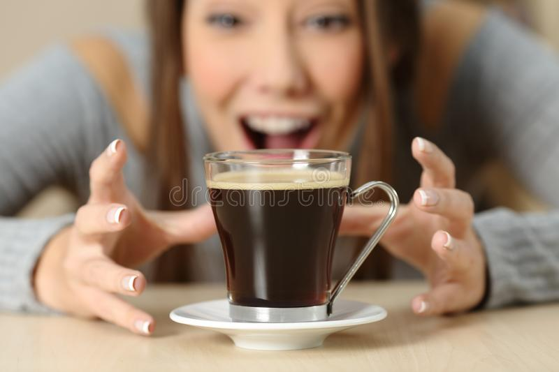 Amazed woman looking at a coffee cup. Front view close up of an amazed woman looking at a coffee cup with crave royalty free stock image