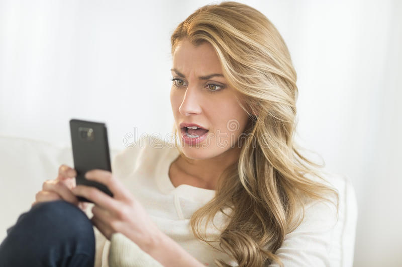 Download Amazed Woman Looking At Mobile Phone On Sofa Stock Photo - Image of mouth, open: 32278518