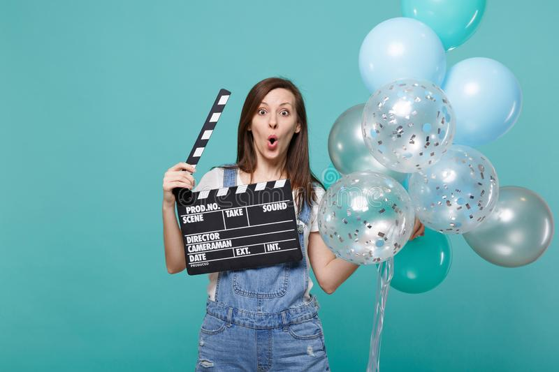 Amazed woman with opened mouth hold classic black film making clapperboard celebrating with colorful air balloons stock photo