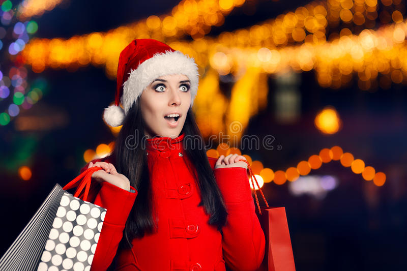 Amazed Woman With Shopping Bags in Christmas Fair stock photo