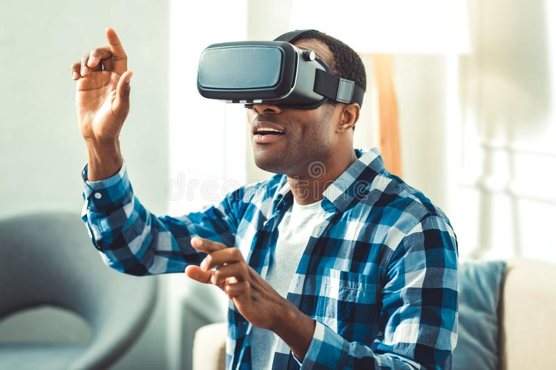 Amazed young afro american man experiencing VR. VR technologies. Attractive afro american man wearing VR headset and gesturing stock photo