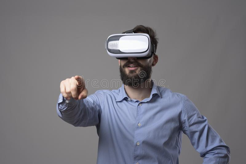 Amazed young bearded adult business man with vr headset touching virtual digital touch screen royalty free stock image
