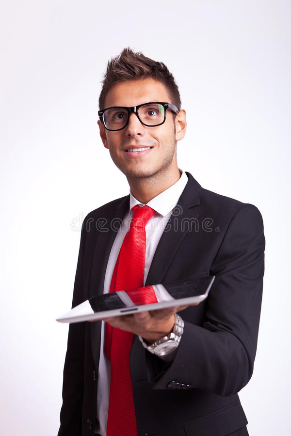 Amazed young business man holding a pad