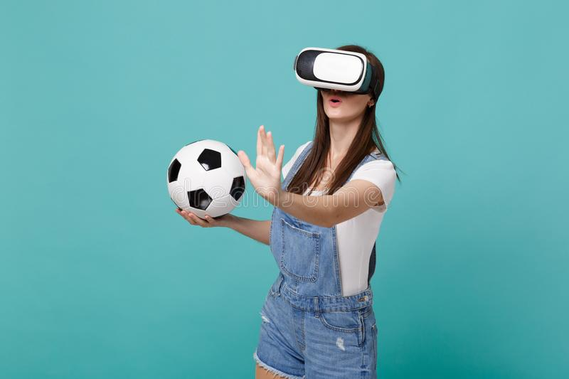 Amazed young girl football fan looking in headset holding soccer ball playing touch something like push click on button royalty free stock images
