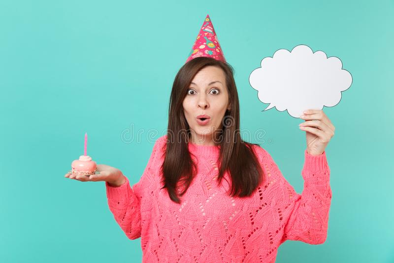 Amazed young woman in birthday hat hold in hand cake with candle, empty blank Say cloud speech bubble for promotional. Content isolated on blue background stock photo