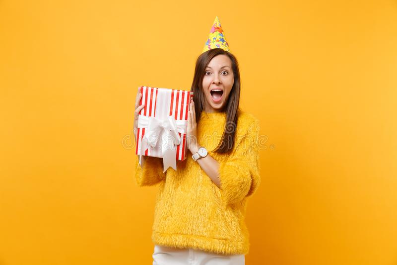 Amazed young woman in birthday party hat hold red box with gift present celebrating enjoying holiday isolated on bright. Yellow background. People sincere royalty free stock images