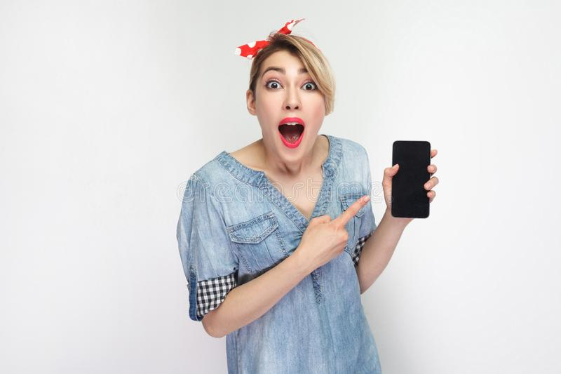 Amazed young woman in casual blue denim shirt, red headband standing, holding and pointing finger to cell phone with opened mouth royalty free stock photos