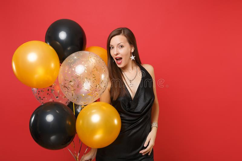 Amazed young woman in little black dress celebrating holding air balloons isolated on red background. St. Valentine`s royalty free stock image