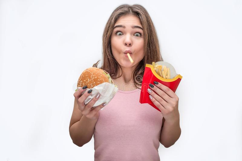 Amazed young woman look on camera and eat fried potatoes. She hold burger in hands as well. Isolated on grey background. Amazed young woman look on camera and stock photo
