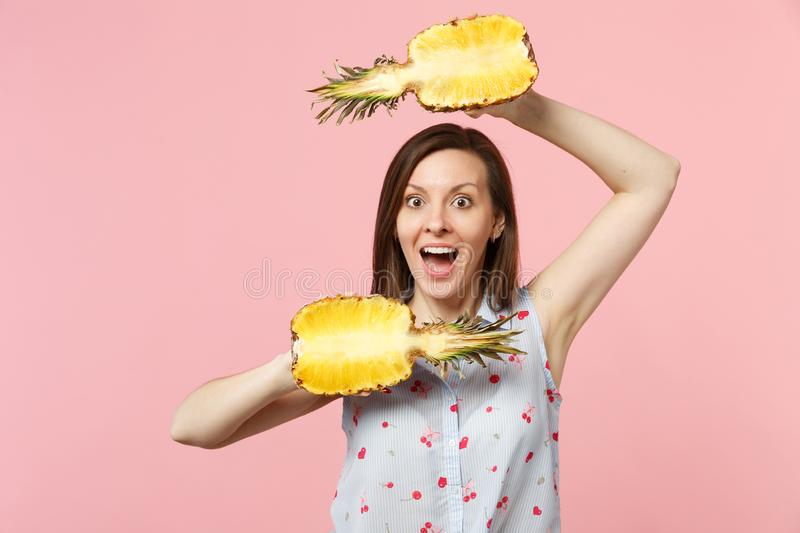 Amazed young woman in summer clothes keeping mouth open hold halfs of fresh ripe pineapple fruit isolated on pink pastel stock images