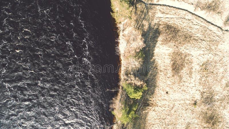 Amazing aerial shot of beautiful dark river shore. Forest background. Amazing aerial shot of beautiful dark river shore - early spring colors stock photography