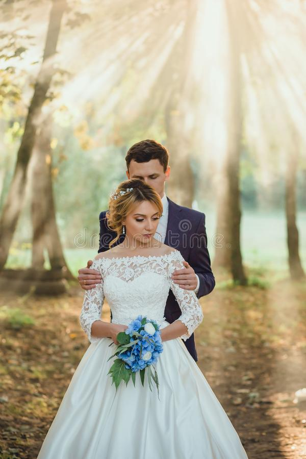 Amazing attractive young couple in wedding day. bride in elegant white long dress and blue bouquet in hand, groom in a stock photography