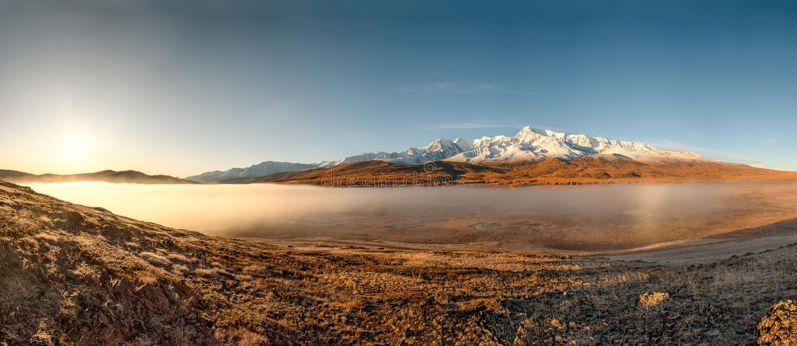 Mountains fog sun sunrise autumn panorama. Amazing autumn panorama with the sun, mountains covered with snow and a golden forest, white fluffy fog over the lakes royalty free stock image