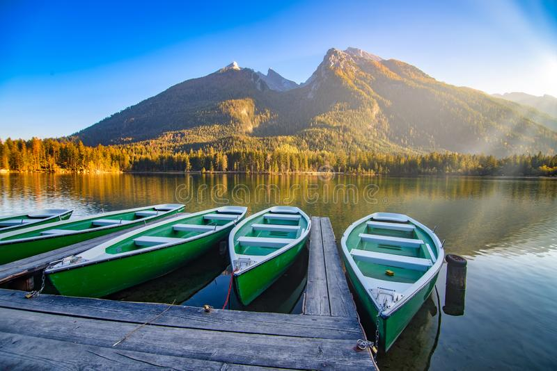 Amazing autumn scenery on Hintersee lake with boats moored on wooden pier, Bavaria, Germany stock image