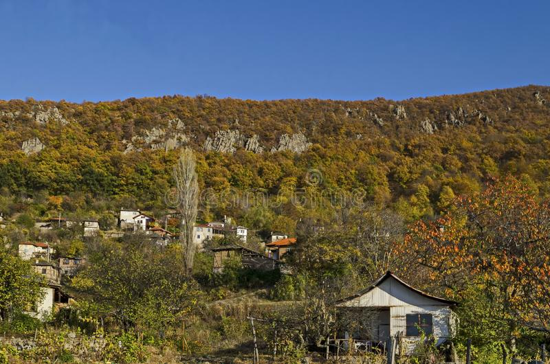 Amazing autumn view of glade, hill, forest with deciduous trees and residential district of the pretty village Zhrebichko. Bratsigovo municipality,  Rhodope royalty free stock photography