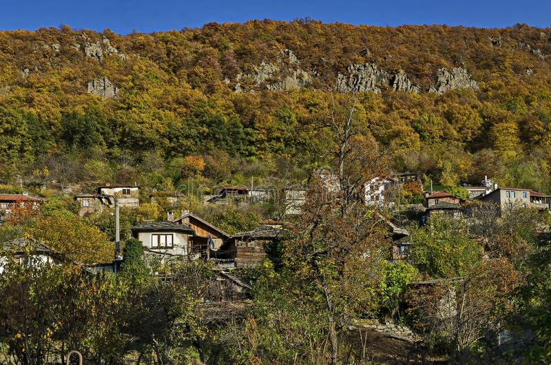 Amazing autumn view of glade, hill, forest with deciduous trees and residential district of the pretty village Zhrebichko. Bratsigovo municipality,  Rhodope stock image