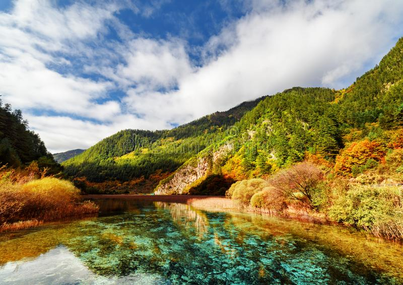 Amazing azure crystal clear water of river and mountains in fall. Amazing azure crystal clear water of river and mountains in autumn, Jiuzhaigou nature reserve ( stock photo