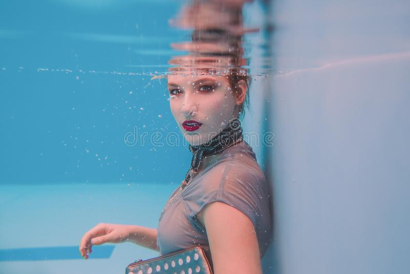 Amazing beautiful art surreal portrait of young woman in grey dress and beaded scarf underwater royalty free stock images