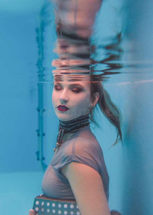 Amazing beautiful art surreal portrait of young woman in grey dress and beaded scarf underwater. In the swimming pool royalty free stock images