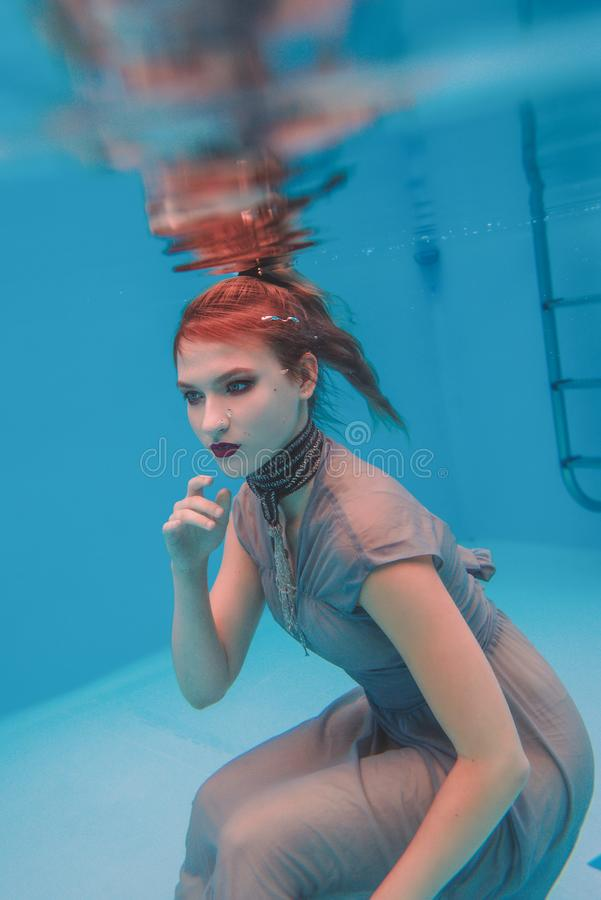 Amazing beautiful art surreal portrait of young woman in grey dress and beaded scarf underwater. In the swimming pool royalty free stock photo