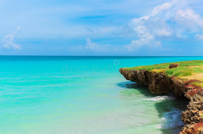 Amazing beautiful landscape view on tranquil turquoise ocean and cliff with blue cloudy sky background stock image