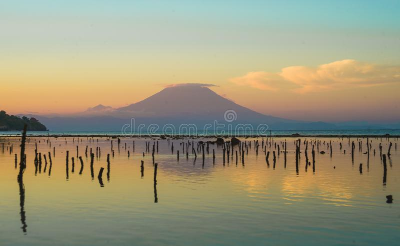 Amazing beautiful scenic view from the beach of of active volcano Mount Agung in Bali island of Indonesia on sunset in Asia travel royalty free stock photo