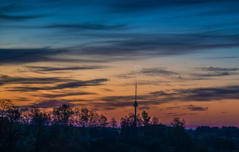 Amazing beautiful sunrise sky over forest. And tv tower in Vilnius, Lithuania stock photos