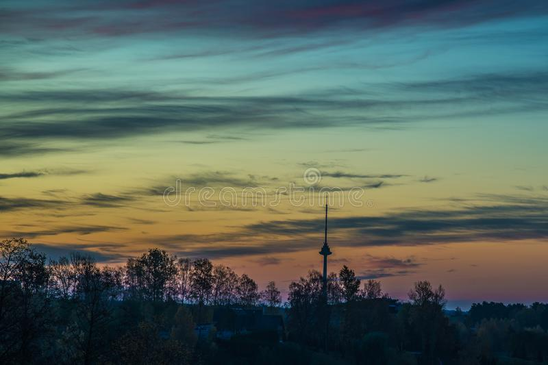 Amazing beautiful sunrise sky over forest. And tv tower in Vilnius, Lithuania royalty free stock photography