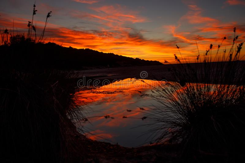 Amazing blazing sunset landscape over the island and the sky above it with an awesome sun. sunset view on the beach stock images