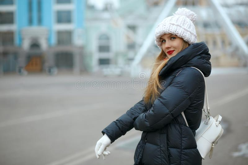 Amazing blonde model with red lipstick wearing knitted cap, enjoying city walk. Empty space royalty free stock photo