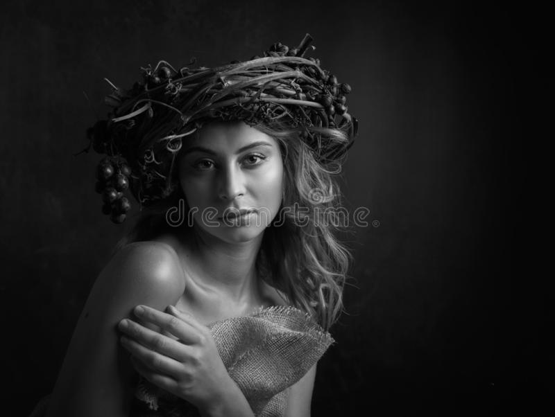 Amazing blonde woman portrait. Beautiful girl with long wavy hair. Vine wreath with blue grapes on a head. Copy space, black and. White royalty free stock photography