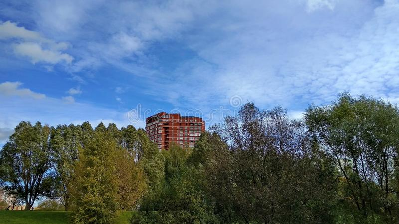 Lonely house on the hill. Amazing blue sky with rare clouds, skyscraper on the hill surrounded with trees royalty free stock photos