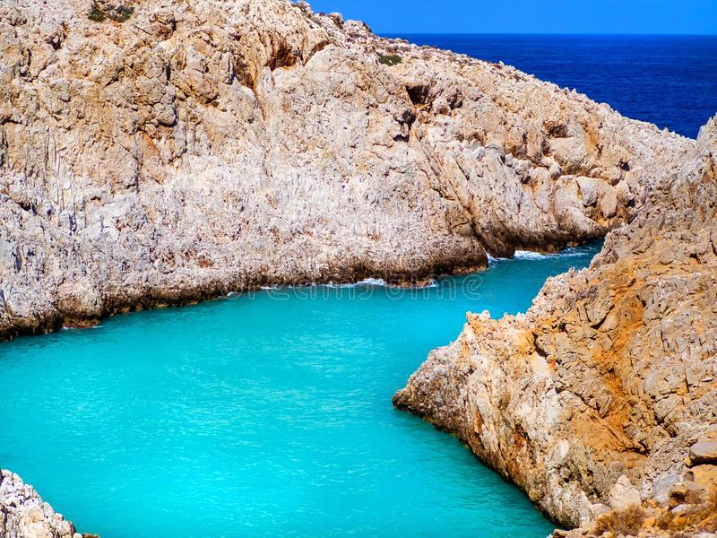 Amazing bright blue water in a secluded cove with orange cliffs surrounding it - Crete, Greece stock photography