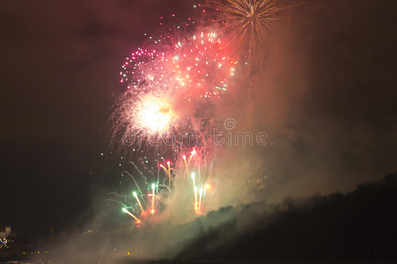 Amazing bright red,green and yellow firework celebration of the new year 2015 in Prague over the metronome sculpture royalty free stock image