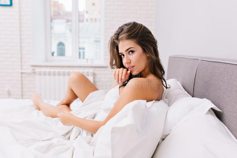 Amazing charming girl with long brunette hair chilling in white bed in modern apartment. Sexy look, positive emotions. Waking up in the morning, good mood royalty free stock images