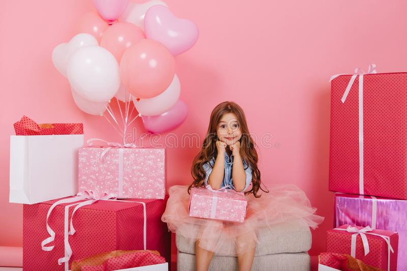Amazing charming joyful little girl sitting with present suround big giftboxes, balloons on pink background. Happy. Celebration birthday party in childhood royalty free stock images