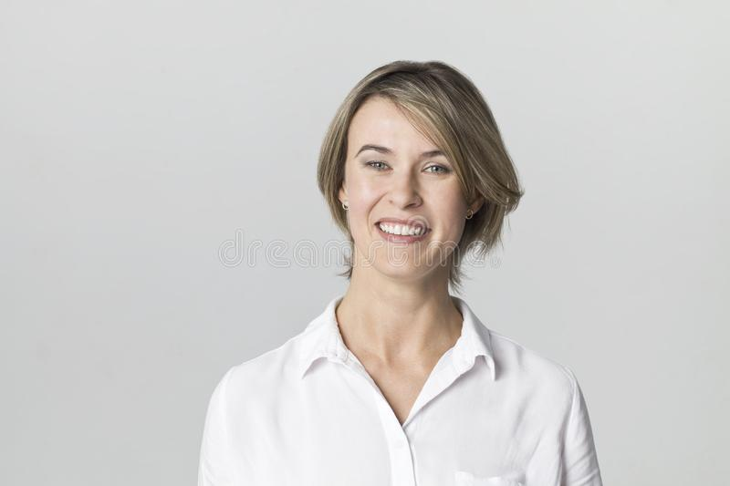 Amazing and cheerful smiling blonde in white shirt studio shot, isolated on white stock photography