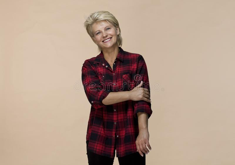 Smiling positive female with attractive look, wearing checked shirt, posing against colored background royalty free stock image