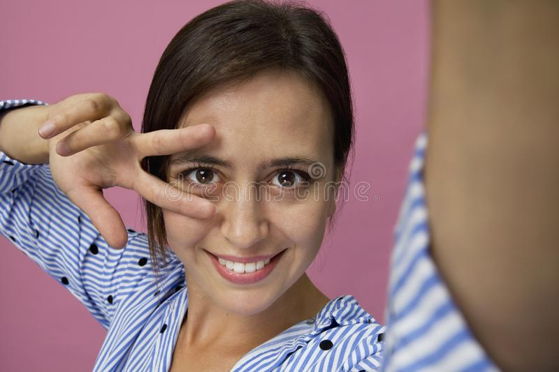Smiling positive female close up with attractive look posing against pink background. Taking a selfie royalty free stock image