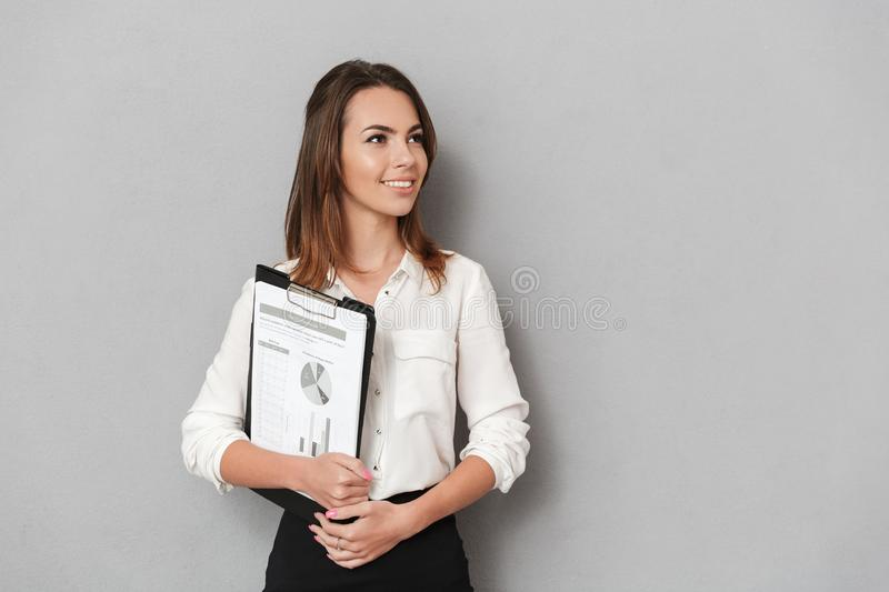 Amazing cheerful young business woman holding clipboard. Image of an amazing cheerful young business woman standing over grey wall background holding clipboard stock photos