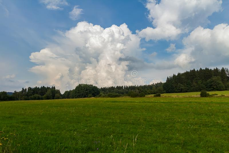 Amazing cloud with blue sky, summer czech meadow with trees, Sumava national park.  stock photo