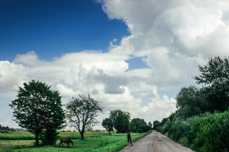 Amazing clouds on blue sky and country side with girl and horse, beautiful summer nature landscape royalty free stock photos