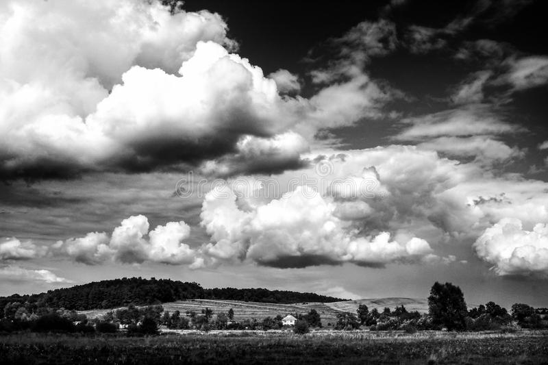 Amazing clouds on sky and country side, beautiful summer nature. Landscape, black and white royalty free stock photo
