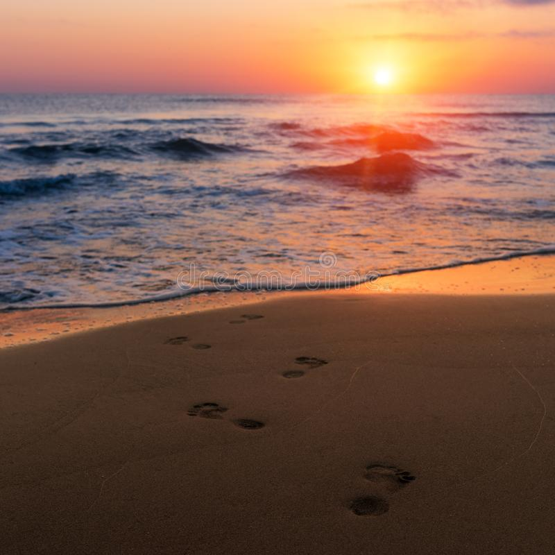 Amazing colorful sunrise at sea, footprints in the sand stock photo