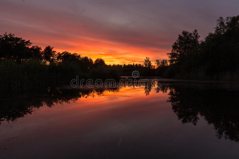 Amazing coloured sunset in Waterschei near Genk, Belgium. Sunset in the national park near Waterschei in Genk, Belgium with amazing colors in the sky. The park stock photo