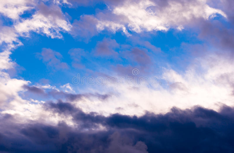 Amazing contrast white and dark clouds and clear blue sky. Beautiful celestial panorama cloudy sky with torn white and gray with dark clouds lit by the sun with stock image