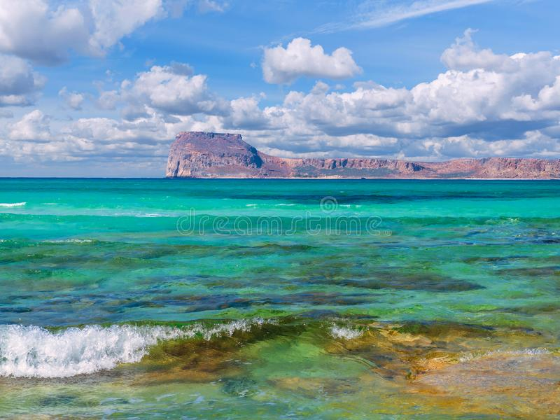 Amazing crystal clear blue water on a paradise beach - small wave - rocky island in the background royalty free stock images