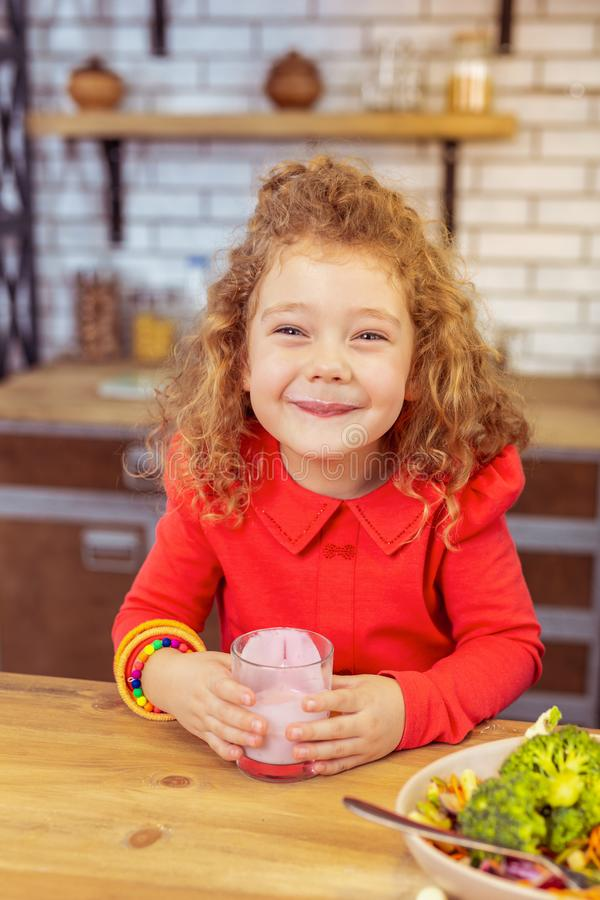 Amazing curly-haired kid spending weekend at home. Be happy. Charming girl expressing positivity while posing on camera royalty free stock images
